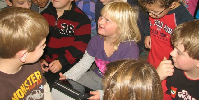 Basehor Elementary School first-grader Piper Rusk tries out a Nook Color tablet device during class Tuesday, as other students look on. The students looked at a device owned by teacher Amy Scruggs while waiting for their own classroom  tablets to arrive, thanks to a $600 grant from the Basehor-Linwood Education Foundation.
