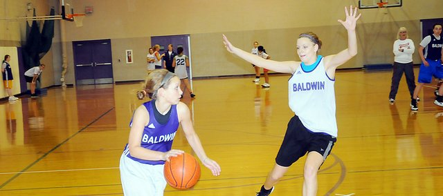 Baldwin High School junior Kailyn Smith, left, dribbles around junior Glenn McCabe during practice Tuesday afternoon. Smith is one of two returning starters from last year's Bulldogs' squad. Baldwin opens the season at 6 p.m. Friday at home.