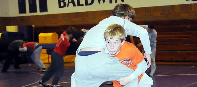 Baldwin High School sophomore Tucker Clark, right, takes down junior Bryce Shoemaker during practice Tuesday. The Bulldogs will kick off the season at 9 a.m. Saturday at the Gardner-Edgerton Invitational, which is arguably the hardest tournament of the season.