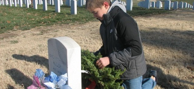 Connor McEnerney, a Basehor Intermediate School fifth-grader, places a wreath on a veteran's headstone Saturday at Leavenworth National Cemetery. Connor's father is a Marine veteran who served in the Gulf War.