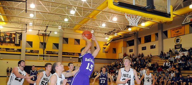 Baldwin High School sophomore Cornell Brown (No. 15) attempts a shot between several Paola players at the end of the third quarter Tuesday. Brown led the Bulldogs with 17 points as they beat Paola 49-42.