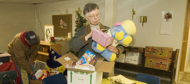 Jim, left, and Janet Stuke sort through gifts for children Monday in Tonganoxie. The Stukes are organizing gifts that families and organizations have donated to Good Shepherd Thrift Shop and Food Bank, which will be given to more than 60 famlies in need in the area.