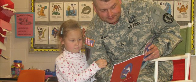 Army Staff Sgt. Timothy Irwin reads to a kindergarten class at Glenwood Ridge Elementary School on Thursday as his daughter Viktoria stands by his side. Irwin, who had been stationed at Fort Bliss in Texas since August, surprised Viktoria on Thursday by appearing in her class.