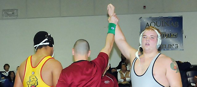 Baldwin High School senior Colton Bonner, right, has his arm raised by the official, acknowledging him as the winner of the 220-pound championship match Saturday. Bonner defeated the Lawrence High wrestler 14-6, winning his first-ever varsity tournament. Bonner is 11-1 on the season after two tournaments.
