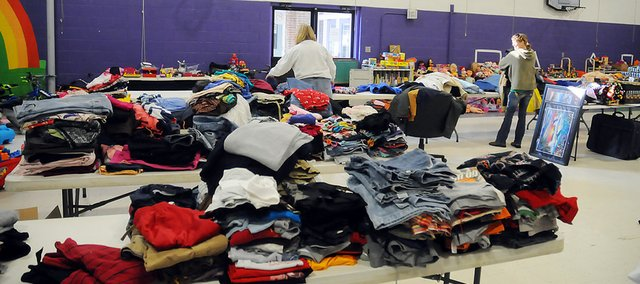 Items donated during the Fill the Bus campaign cover tables Tuesday at the multi-purpose room of the old Baldwin Elementary School at Seventh and Chapel streets. The toys, clothes and other items will be available to Baldwin City residents from 9 a.m. to 3 p.m. Saturday.
