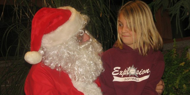 Britney Hoffman, a second-grader at Basehor Elementary School, has a chat with Santa Claus at the Basehor PRIDE Holiday Celebration on Friday, Dec. 16, at Basehor-Linwood Middle School. Britney asked Santa for a RipStik, a skateboard-like object with two wheels.