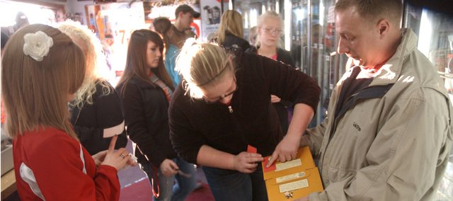 Seventh-grader Gabi Westrich applies a sticker Friday to a cartoon of beer at JR's Liquor Store, warning adults not to provide alcoholic beverages to minors. It was part of a joint Tonganoxie High School Students Against Drunk Driving and Transforming Tonganoxie Together's Sticker Shock campaign, which also placed stickers at Mary's Liquor Store.