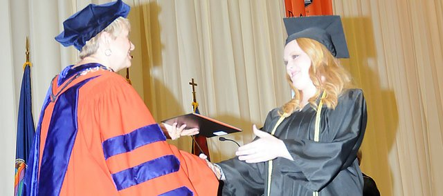Baldwin City's Carly Young receives her bachelor's degree and congratulations from Baker University President Pat Long during Sunday's graduation at the Collins Center. Long handed out 334 degrees at the ceremony.