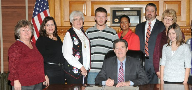 Representatives of the Basehor-Linwood YouthFriends program — including Basehor-Linwood High School junior William Wilson, fourth from left; his YouthFriends mentor, Pat Wolfe, to his right; and YouthFriends coordinator Tammy Potts, far left — are recognized as Gov. Sam Brownback signs a proclamation signifying January as National Mentoring Month in his office in Topeka on Wednesday. Also pictured are Malissa Martin-Wilke, director of Communities In Schools of Kansas, second from left; Michelle Montgomery-Thomas, program consultant for the Kansas Juvenile Justice Authority, behind Brownback; Daniel Soliday, CEO of Kansas Big Brothers Big Sisters; and representatives of the Cowley County Tech Wizards Mentoring Project, a 4-H program.