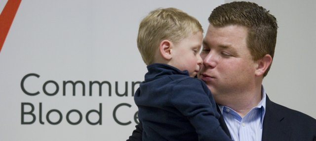 Thomas Charles kisses his son Joseph after a press conference at the Community Blood Center in Kansas City. Joseph Charles, 4, got a chance to meet some of the people Tuesday that had donated blood to help him battle Neuroblastoma.