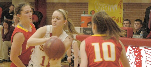 Emily Soetaert tries to make a pass between two Atchison defenders.