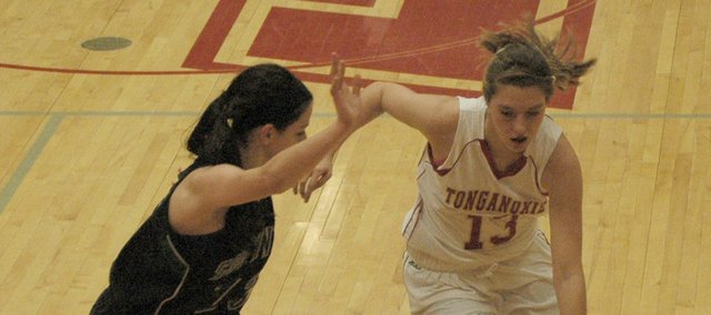 Tonganoxie's Emma Stilgenbauer drives around Blue Valley Southwest's Emily Eldridge. Stilgenbauer tied for the team lead with 10 points.