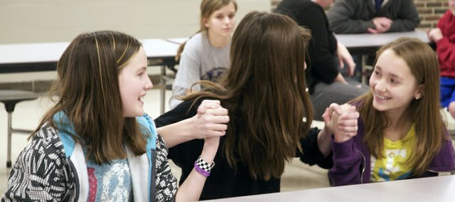 Baldwin Junior High School seventh-graders Alaina Schiffelbein (left), Emma Bailey an Emma McLaren hold hands to encourage each other Friday during the fifth-round of the school's spelling bee. McLaren would eventually win after a long duel with Schiffelbein.