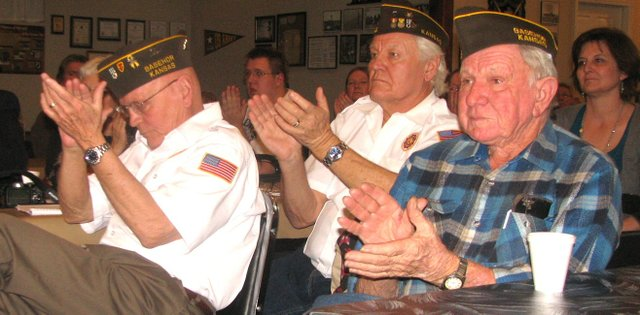 "Basehor VFW Post members — from left, Phil Jenkins, Tom Steele and Robert A. Miller — applaud at the conclusion of BLMS seventh-grader Tucker Rowland's Patriot's Pen essay. ""One reason I am proud of our country is everyone is even,"" Tucker said in his piece. ""No one is treated different."""