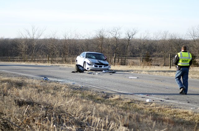 A Douglas County Sheriff's officer Monday morning walks to a car involved in a two-vehicle collision on U.S. Highway 59 about 2 miles north of the intersection with U.S. Highway 56. A Kansas Highway Patrol officer on the scene said both drivers in the wreck suffered minor injuries but refused medical transport.