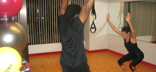 Personal trainer Earnest Jackson reminds Basehor resident Dawn Slavens to keep her arms pointing straight up during a squat exercise in the new group training room at Snap Fitness 24-7 in Basehor on Monday. The new room is part of a 1,000-square-foot expansion completed earlier this year at the gym.