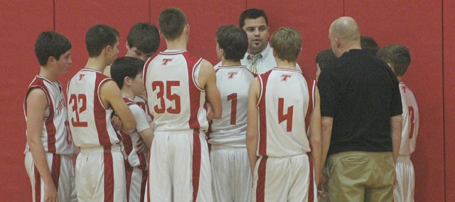 The Warriors get instructions from coach Ryan Scott at halftime.