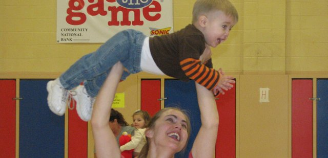 "Sarah Jump of Basehor lifts her 17-month-old son Ethan above her head during the ""walkers"" portion of the Basehor-Linwood Parents as Teachers workout Friday at Basehor Elementary School."