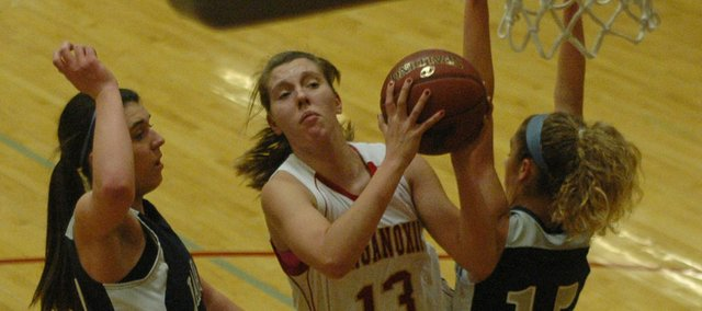 Tonganoxie's Emma Stilgenbauer is fouled by Mill Valley's MacKenzie Koch on her way to the basket.