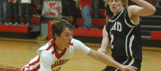 Tonganoxie's Colby Yates drives against Bishop Ward's Evan Brull. Yates finished with 14 points.