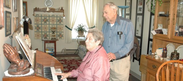 Roberta Daniel, seated, plays the organ that she and her husband, Gerry Daniel, purchased for their 50th Anniversary, as Gerry looks on. The Bonner Springs couple will celebrate their 63rd wedding anniversary Feb. 20.