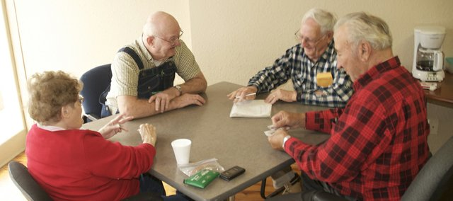 Regular Baldwin City Recreation Commission pinochle players (clockwise from top) Lloyd Bowers, Ed Booth, Truly Schlup and Viola Schlup chuckle as Booth adds up the score after a hand. The BCRC offers games at noon weekdays as a social outlet.