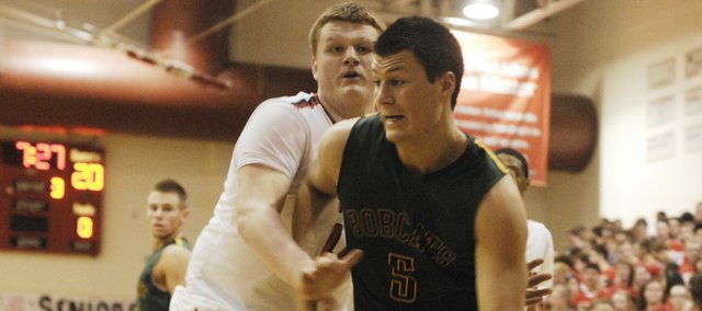 Basehor-Linwood junior Ben Johnson dribbles past Lansing senior Mike Miller in the second half of the Bobcats' 52-44 victory on Friday.