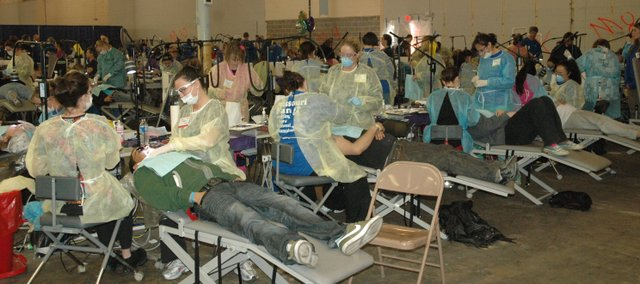 Volunteer dentists and hygienists perform general cleanings Saturday on some of the thousands who showed up at the two-day Kansas Mission of Mercy free dental clinic in the former WalMart building at State Avenue and 65th Street in Kansas City, Kan. The clinic had the capacity to treat 1,200 each day, so some were turned away.