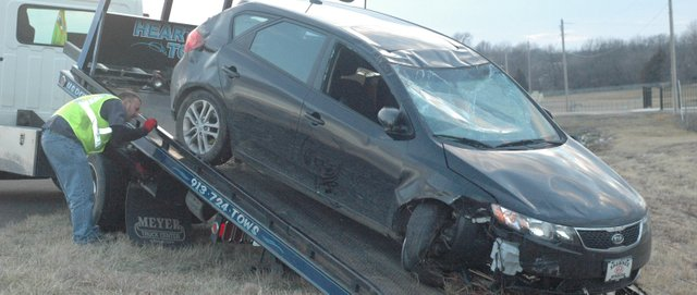 A tow-truck operator loads up a damaged 2011 Kia SUV after a rollover accident on U.S. Highway 24-40 just west of Basehor late Monday afternoon.