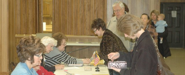 Basehor voters sign in and present their photo IDs to election workers Tuesday morning at Holy Angels Catholic Church, where polling for the Basehor recall election was taking place. Workers said voter turnout so far had been similar to a typical city election, if not a bit lower.