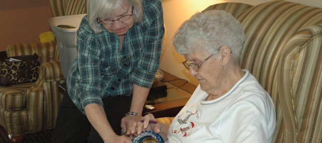 "Peggy Stuart, left, helps Marie Kirk learn how to use the ""Knifty Knitter"" with the Missions for Newborns group at Nettleton Manor."