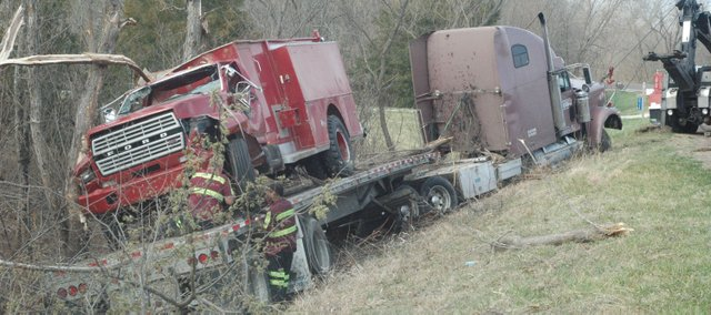 Crews work to remove a semi-trailer carrying a fire truck Thursday morning from the east ditch of U.S. Highway 24-40 about 5 miles south of Tonganoxie.