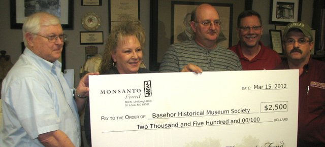 Basehor Historical Museum board chairman Ken Massingill (from left) and museum director Carla Crawford accept a $2,500 donation from farmer Mel Theno (center) and the Monsanto Company. Joining them were Mike Glasnapp, a sales manager for Monsanto (second from right), and Rick Ruzsa, agronomy manager for the Leavenworth County Cooperative Association.