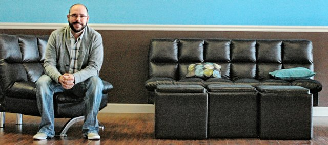 Matt Miller sits in the modernized lobby of New City Church, recently opened in an abandoned movie theater, at 7456 Nieman Road. The lead pastor said he wants the church to make a difference in the community.  