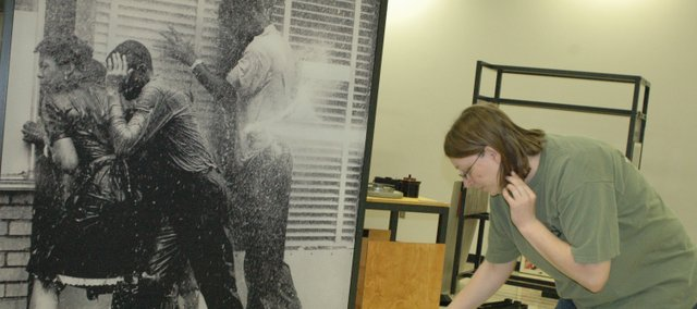"While assembling the exhibit, Michelle Wolfe sorts through exhibit information Monday near an image of civil rights protesters being blasted with a water hose. The ""For All the World to See"" exhibit at the Wyandotte County Historical Museum includes some graphic images from the era of the civil rights movement as well as images of blacks from popular culture. It opens to the public Monday."