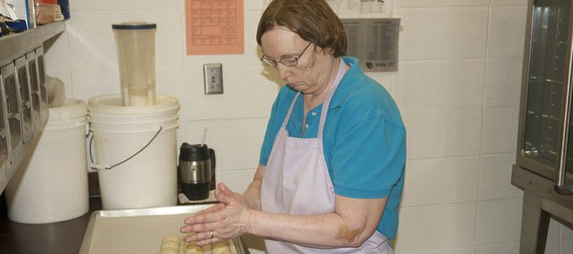 Mary Ruppert molds dinner rolls for baking in the Baldwin Junior High kitchen. Having worked in school lunchrooms and kitchens for 23 years, Ruppert is responsible for all the baked goods served this year in district schools.