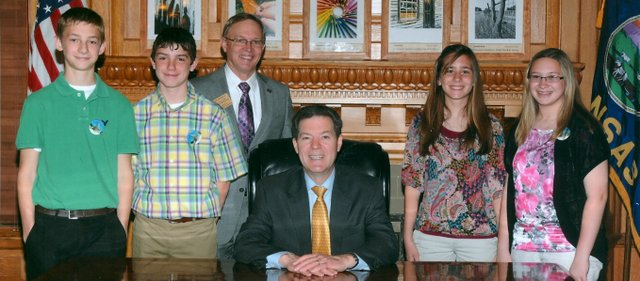 Basehor-Linwood Middle School student Zach McKnight, second from left, is pictured with Rep. Tom Moxley and Gov. Sam Brownback at the state Capitol on March 29. Zach served as a page for Moxley for a day.