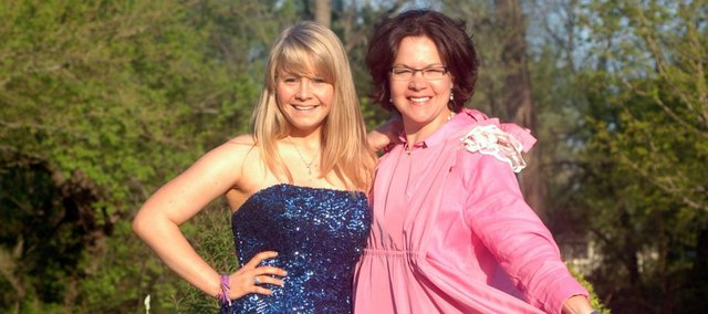 Taylor Clark and her mother, Erica Clark, pose in their dresses for senior prom. Taylor is wearing the dress she'll be donning Saturday for the Tonganoxie High School prom, while Erica is holding the dress she wore for the 1987 THS prom.