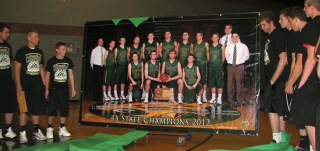 The 2012 BLHS boys basketball team gazes at its state championship banner for the first time, after ripping off a layer of paper to unveil it. The banner was unveiled at a community assembly to honor the team April 18.