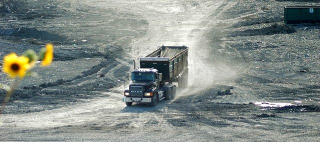 A truck exits the active cell after dropping off a load of waste at the Johnson County Landfill in Shawnee. Hungry gulls converge on the garbage, which is leveled and compacted by heavy machinery as it pours in.
