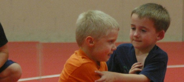 Presley Herrig and Cody Fraedrich practice a wrestling maneuver at last week's youth clinic in the TES gym.
