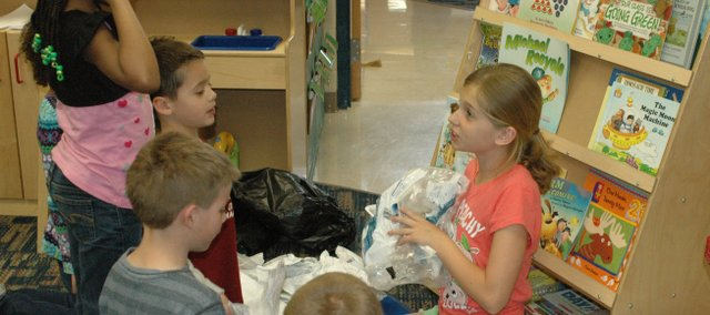 "Ava Modine helps kindergarteners pick out which items from a bag of ""trash"" are recycleable."