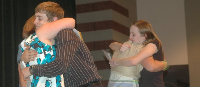 In the Basehor-Linwood High School auditorium April 25, Russell Clark and Sarah Hopkins hug Amber (left) and Vera Gaffney, the younger sister and mother of Joshua Gaffney, who died in a car accident in 2008 as a Basehor-Linwood Middle School eighth-grader. Clark and Hopkins were the 2012 winners of a scholarship set up by the family in Joshua's memory. Joshua would have been a member of the BLHS 2012 graduating class along with them.