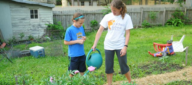 Jill Boyle waters flowers in the backyard of her Baldwin City home while her 9-year-old daughter Josephine watches. The annuals Boyle is growing in her backyard garden and in a larger plot near the Baker University stadium produce buckets of color she will take to the Baldwin City Farmers Market this summer.
