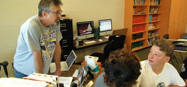 Basehor-Linwood Middle School reading teacher Tom Cooper talks with eighth-graders Jaymez Turner (left) and Sam Giomi during class Monday. Cooper will retire from teaching at the end of the school year after 33 years in Basehor-Linwood schools, though he will stay on as a coach and athletic director.