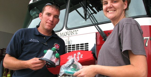 Brandon Roberts, a fire inspector for the Fairmount Township Fire Department in Basehor, accepts a set of pet oxygen masks from Wagg'n Tails Day Spa and its clients, presented by owner Amber Anderton, on Friday.