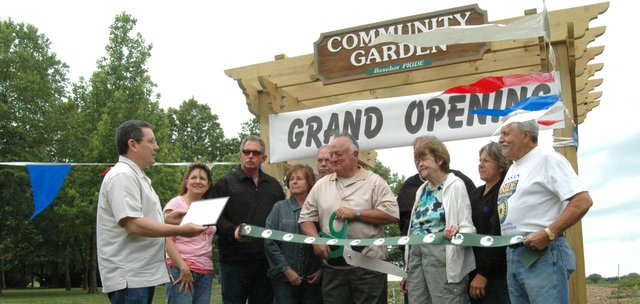 Basehor PRIDE member Orville Stokes prepares to snip the ceremonial ribbon at the Basehor Community Garden's grand-opening event May 12. All the touches were in place at the garden's entrance for the first time.