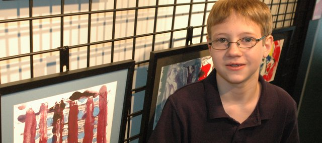 Justin Roberts, 13, of Bonner Springs, stands near one of his two prints currently on display at The New Theatre Restaurant in Overland Park. The exhibit features the artwork of Justin and his classmates at Horizon Academy, a private school for students with learning disabilities in Roeland Park.