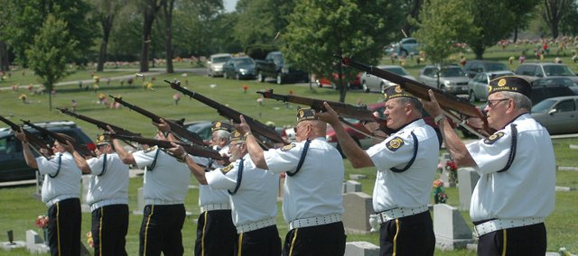 Shell casings fly as eight members of the Shawnee American Legion Post 327 Honor Guard their M1 rifles during May 17 graveside services for an 83-year-old Army veteran at Maple Hill Cemetery in Kansas City, Kan. The 24 casings produced by the gun salute, as well as a flag that draped his coffin, were presented to the veteran's family members as remembrances.