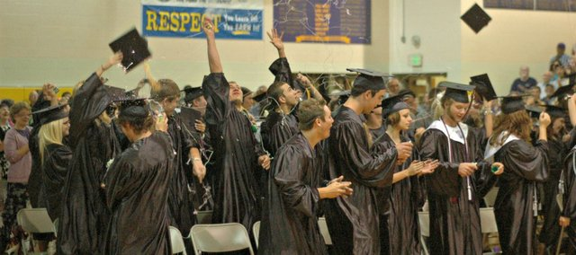 Members of the McLouth High class of 2012 throw their caps and bombard each other with aerosol string Saturday as they are officially introduced as high school graduates.